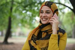 Νέα μουσουλμανική γυναίκα που μιλά με το έξυπνο τηλέφωνο Στοκ Φωτογραφία