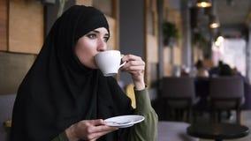 Νέα μουσουλμανική γυναίκα που φορά τη μαύρη συνεδρίαση hijab στο σύγχρονο καφέ Κατανάλωση του καφέ από το άσπρο φλυτζάνι και σκεπ φιλμ μικρού μήκους