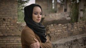 Νέα μουσουλμανική γυναίκα πρόσφυγας στο hijab που στέκεται κοντά στο κτήριο και που εξετάζει τη κάμερα με εκφοβισμένος και φοβισμ φιλμ μικρού μήκους