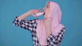 Νέα μουσουλμανική γυναίκα στο hijab που έχει το πρόβλημα με τον επώδυνο λαιμό, ψεκασμός χρήσεων για να μεταχειριστεί το λαιμό απόθεμα βίντεο