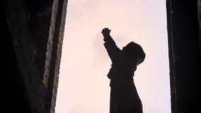 Νέα μουσουλμανική γυναίκα στο hijab που αυξάνει τα χέρια της στον ουρανό και που προσεύχεται στο εγκαταλειμμένο κτήριο, που εκφοβ φιλμ μικρού μήκους