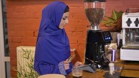 Νέα μουσουλμανική γυναίκα στο hijab που κάνει την πληρωμή με πιστωτική κάρτα, που παίρνει τον καφέ και που πηγαίνει μακριά, χαμόγ απόθεμα βίντεο