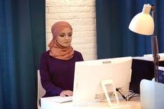 Νέα μουσουλμανική γυναίκα που εργάζεται σε έναν υπολογιστή Στοκ Εικόνα