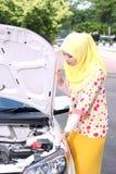 Νέα μουσουλμανική γυναίκα που ελέγχει τη μηχανή Στοκ εικόνα με δικαίωμα ελεύθερης χρήσης