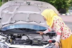 Νέα μουσουλμανική γυναίκα που ελέγχει τη μηχανή Στοκ Φωτογραφίες