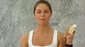 Νέα μπανάνα εκμετάλλευσης γυναικών, που τρώει την που εξετάζει τη κάμερα Στοκ φωτογραφίες με δικαίωμα ελεύθερης χρήσης