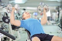Νέα μυϊκά αρσενικά βάρη ανύψωσης σε μια γυμναστική Στοκ Φωτογραφία