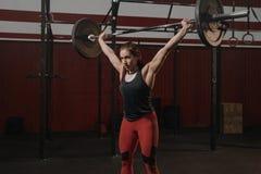 Νέα μυϊκή γυναίκα που κάνει τις weightlifting ασκήσεις στη γυμναστική crossfit στοκ εικόνα με δικαίωμα ελεύθερης χρήσης