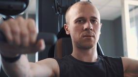Νέα μυϊκή κατάρτιση ατόμων σκληρά στη μηχανή κωπηλασίας στο στούντιο ικανότητας φιλμ μικρού μήκους