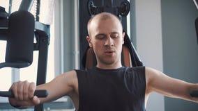 Νέα μυϊκή κατάρτιση ατόμων σκληρά στη μηχανή κωπηλασίας στο στούντιο ικανότητας απόθεμα βίντεο