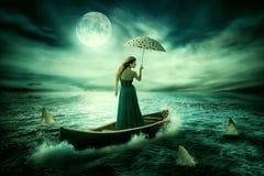Νέα μόνη γυναίκα με την ομπρέλα που παρασύρει στη βάρκα μετά από τη θύελλα που περιβάλλεται από τους καρχαρίες Στοκ εικόνες με δικαίωμα ελεύθερης χρήσης