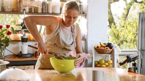 Νέα να ζυμώσει γυναικών ζύμη για το σπιτικό ψωμί στο πράσινο πλαστικό κύπελλο στοκ φωτογραφίες