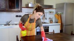 Νέα νοικοκυρά που καθαρίζει τα έπιπλα στην κουζίνα απόθεμα βίντεο