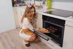 Νέα νοικοκυρά που παίρνει cupcakes από το φούρνο Στοκ Εικόνες