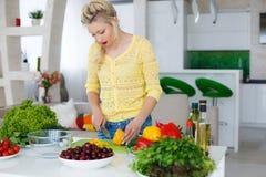 Νέα νοικοκυρά που προετοιμάζει τη σαλάτα στην κουζίνα Στοκ Φωτογραφίες