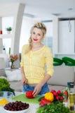 Νέα νοικοκυρά που προετοιμάζει τη σαλάτα στην κουζίνα Στοκ Εικόνες