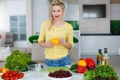 Νέα νοικοκυρά που προετοιμάζει τη σαλάτα στην κουζίνα Στοκ Εικόνα
