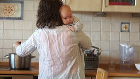 Νέα νοικοκυρά που προετοιμάζει το γεύμα στην κουζίνα Μια γυναίκα κρατά ένα μωρό σε ετοιμότητα της Πολλαπλών καθηκόντων - ταΐζει τ απόθεμα βίντεο