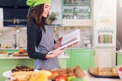 Νέα νοικοκυρά που προσπαθεί να βρεί μια νέα συνταγή στο cookbook στεμένος στον πίνακα με τα τρόφιμα και τα συστατικά στοκ εικόνες