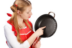 Νέα νοικοκυρά στην κόκκινη ποδιά με τα αστεία ponytails που κρατούν το τηγάνισμα Στοκ εικόνες με δικαίωμα ελεύθερης χρήσης