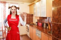 Νέα νοικοκυρά στη φωτεινή κόκκινη ποδιά με τις αστείες στάσεις ponytails Στοκ Εικόνες