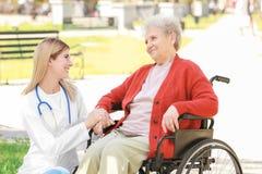 Νέα νοσοκόμα και με ειδικές ανάγκες ηλικιωμένη γυναίκα στην αναπηρική καρέκλα υπαίθρια Στοκ Φωτογραφίες