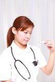 Νέα νοσοκόμα με το θερμόμετρο Στοκ Φωτογραφίες
