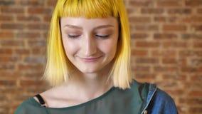 Νέα ντροπαλή γυναίκα με την κίτρινη τρίχα που εξετάζει τη κάμερα και το χαμόγελο, το υπόβαθρο τουβλότοιχος, εύθυμος και ευτυχής απόθεμα βίντεο