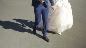 Νέα νύφη εκμετάλλευσης νεόνυμφων σε ετοιμότητα και το περπάτημα Νύφες, που περπατούν κάτω από την οδό που κρατά το χέρι κοντά στο απόθεμα βίντεο