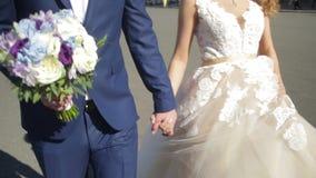 Νέα νύφη εκμετάλλευσης νεόνυμφων σε ετοιμότητα και το περπάτημα Νύφες, που περπατούν κάτω από την οδό που κρατά το χέρι κοντά στο φιλμ μικρού μήκους
