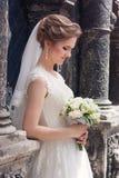 Νέα νύφη με τις στάσεις γαμήλιων ανθοδεσμών Στοκ φωτογραφίες με δικαίωμα ελεύθερης χρήσης