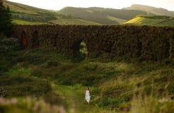 Νέα νύφη που τρέχει κοντά στο χλοώδες brickwall στο πράσινο τοπίο του νησιού του Miguel Σάο στοκ εικόνα