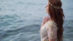 Νέα νύφη στην παραλία κοντά στη θάλασσα στο βράδυ ή Ρομαντικός κοντινός ωκεανός φιλμ μικρού μήκους