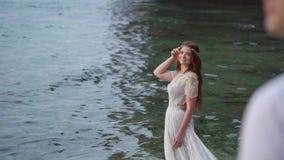 Νέα νύφη στην παραλία κοντά στη θάλασσα στο βράδυ ή Ρομαντικός κοντινός ωκεανός απόθεμα βίντεο