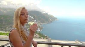 Νέα ξανθή γυναίκα με το κρασί στο εστιατόριο σε Ravello απόθεμα βίντεο