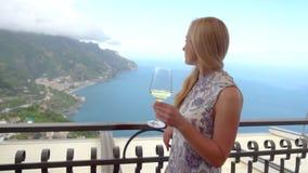 Νέα ξανθή γυναίκα με το κρασί στο εστιατόριο σε Ravello φιλμ μικρού μήκους