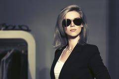 Νέα ξανθή γυναίκα μόδας στα γυαλιά ηλίου στο εσωτερικό λεωφόρων στοκ εικόνα