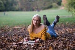 Νέα ξανθή γυναίκα που βάζει στο έδαφος και που διαβάζει ένα βιβλίο στο πάρκο στοκ εικόνες