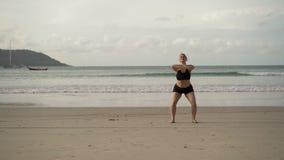 Νέα ξανθή γυναίκα που κάνει τις αθλητικές ασκήσεις σε μια παραλία απόθεμα βίντεο