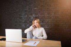 Νέα ξανθή γυναίκα που καλεί με το κινητό τηλέφωνο ενώ το αρχείο αναμονής μεταφορτώνει στο φορητό προσωπικό υπολογιστή στοκ φωτογραφίες