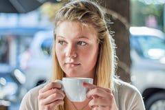 Νέα ξανθή γυναίκα που κρατά μια άσπρη συνεδρίαση φλυτζανιών καφέ στον καφέ Στοκ Εικόνες