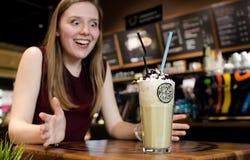 Νέα ξανθή γυναίκα που μένει καταπληκτική στον τοπικό καφέ στο ξύλινο επιτραπέζιο ποτό FR Στοκ Φωτογραφίες