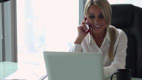 Νέα ξανθή γυναίκα που μιλά στο τηλέφωνο στο γραφείο απόθεμα βίντεο