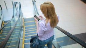 Νέα ξανθή γυναίκα που οδηγά στην κυλιόμενη σκάλα υπόγεια και που χρησιμοποιεί το έξυπνο τηλέφωνο φιλμ μικρού μήκους
