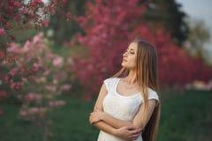 Νέα ξανθή γυναίκα που στέκεται σε έναν ανθίζοντας κήπο ανθίζοντας κεράσι Εύθυμη γυναίκα στο άσπρο φόρεμα που χαμογελά και που κοι Στοκ εικόνα με δικαίωμα ελεύθερης χρήσης