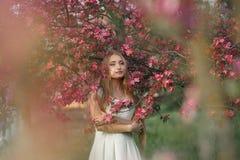 Νέα ξανθή γυναίκα που στέκεται σε έναν ανθίζοντας κήπο ανθίζοντας κεράσι όμορφη γυναίκα πορτρέτου Κλείστε επάνω του προσώπου γυνα Στοκ Εικόνα