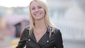 Νέα ξανθή γυναίκα που στέκεται στην οδό και που εξετάζει τη κάμερα Το κορίτσι κοιτάζει σοβαρά και αρχίζει έπειτα να χαμογελά φιλμ μικρού μήκους