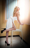 Νέα ξανθή γυναίκα που τυλίγεται στην άσπρη πετσέτα που κοιτάζει στο παράθυρο. Όμορφη νέα γυναίκα με μια πετσέτα γύρω από το σώμα τ Στοκ φωτογραφία με δικαίωμα ελεύθερης χρήσης