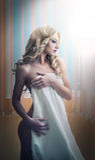 Νέα ξανθή γυναίκα που τυλίγεται στην άσπρη τοποθέτηση πετσετών που χαλαρώνουν. Όμορφη νέα γυναίκα με μια πετσέτα γύρω από το σώμα  Στοκ Φωτογραφία