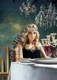 Νέα ξανθή γυναίκα που φορά την κορώνα στο εσωτερικό πολυτέλειας νεράιδων με το em Στοκ εικόνες με δικαίωμα ελεύθερης χρήσης